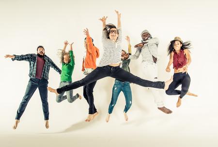 Multi-etnische groep van vrienden springen op een witte achtergrond, studio-opname Stockfoto