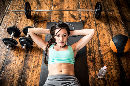 laying abs exercise: Woman working out on the floor Stock Photo