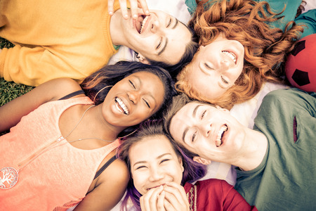 multiracial children: Group of  friends laughing out loud outdoor, sharing good and positive mood.