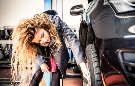 imperfection: Woman and her car at the garage Stock Photo