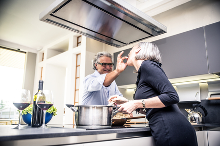 Senior couple cooking and having fun in the kitchen