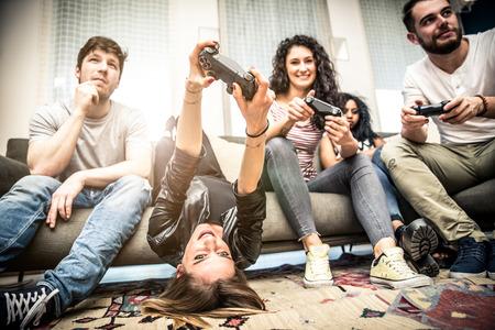 Vrienden die pret op de bank met videospelletjes