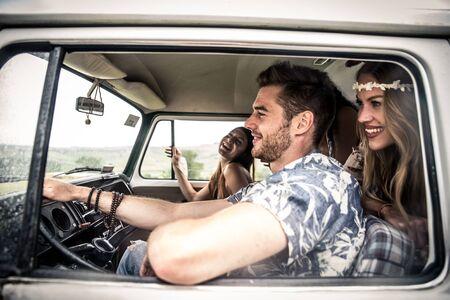 minivan: Hippie friends driving on a minivan