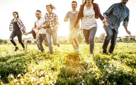 Group of friends running happily together in the grass Stockfoto