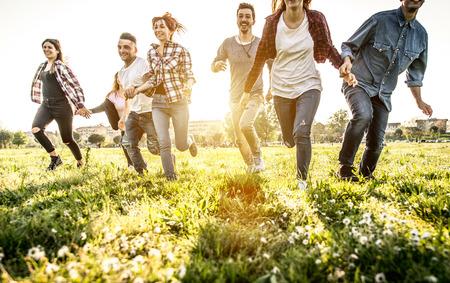 Gruppo di amici in esecuzione felicemente insieme nell'erba Archivio Fotografico - 66397513