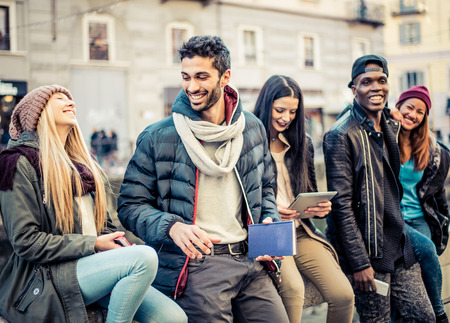 university: Group of multi-ethnic friends walking on the streets and smiling - Young people having fun outdoors