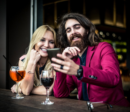bar: Cheerful couple drinking aperitif in a cocktail bar and having a pleasant conversation - Friends taking selfie with phone