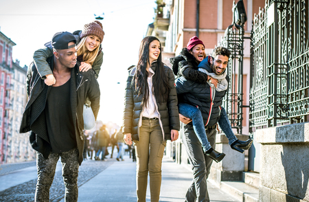 urban people: Group of multi-ethnic friends walking on the streets and smiling - Young people having fun outdoors