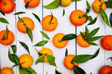 Tangerines with leaves  on white wooden background