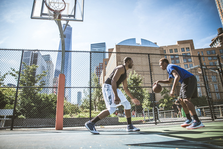 young male: Two afroamerican athlethes playing basketball outdoors - Basketball athlete training on court in New York Stock Photo