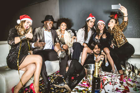 the end of the year: Multi-ethnic group of friends celebrating the end of the year in a nightclub - Sylvester party, clubbers having party on new years eve Stock Photo