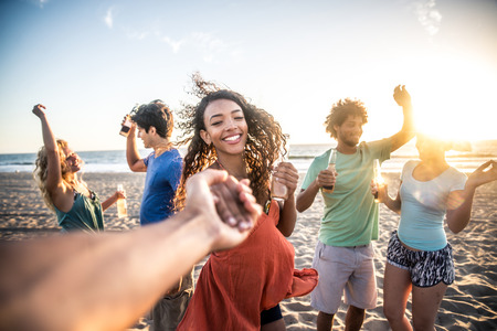 Multi-ethnic group of friends partying on the beach at sunset, pov prospective - Woman taking his boyfriend to dance Stock Photo