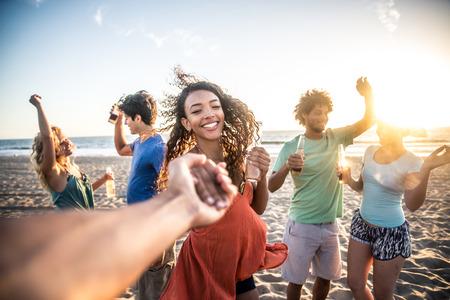 Multi-etnische groep van vrienden feesten op het strand bij zonsondergang, POV aspirant - Vrouw nemen van zijn vriend om te dansen