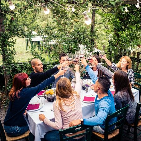 restaurante italiano: Grupo de amigos en el restaurante al aire libre - Las personas que tienen la cena en un jardín