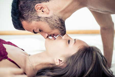 Couple kissing in bed Stock Photo
