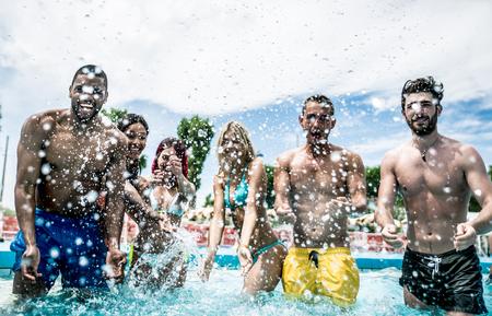 Grupo de amigos haciendo fiesta en la piscina Foto de archivo - 66918039