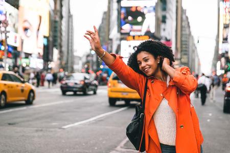 Vrouw op zoek naar een taxi in New York City Stockfoto