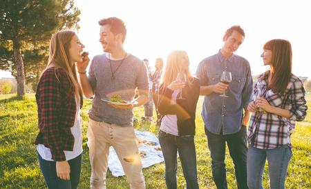 一群朋友在野餐的时候吃和喝-快乐的人在烧烤派对