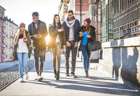 Groep multi-etnische vrienden op straat te lopen en glimlachen - Jonge mensen die pret hebben in openlucht