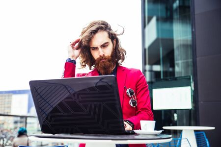 man with beard: Young hipster man working at pc laptop in a cafè outdoors Stock Photo