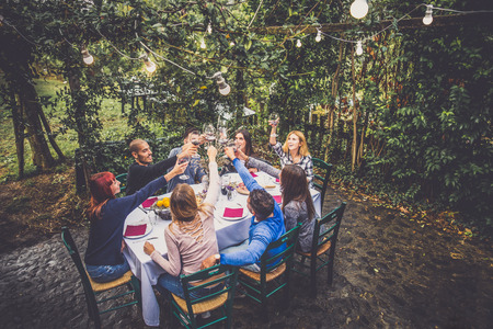 family and friends: Group of friends at restaurant outdoors - People having dinner in a home garden