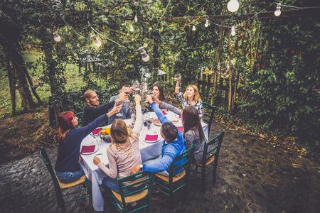 Gruppe von Freunden im Restaurant im Freien - mit Menschen Abendessen in einem Hausgarten Standard-Bild