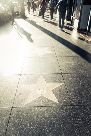 HOLLYWOOD, CA - OCTOBER 12, 2016: People visit Walk of Fame in Hollywood. Hollywood Walk of Fame features more than 2,500 stars with inscribed celebrity names.