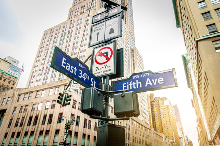 Teken van de straat van Fifth Avenue en East 34th Street in de voorkant van de Empire State Building Stockfoto