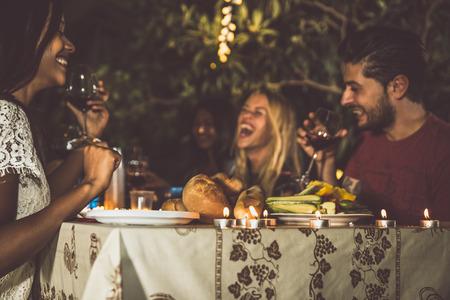 Groep vrienden het maken van een barbecue in de achtertuin tijdens het diner Stockfoto