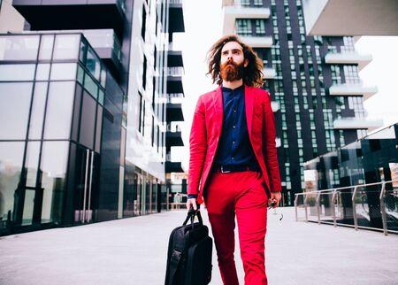 uomo rosso: Moda ritratto di un giovane uomo pantaloni a vita bassa camminare all'aperto con un abito formale rosso - uomo d'affari insolito andare a lavorare