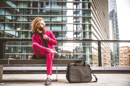 uomo rosso: Moda ritratto di un giovane hipster, seduto su una panchina all'aperto con un abito formale rosso - uomo d'affari insolito andare a lavorare Archivio Fotografico