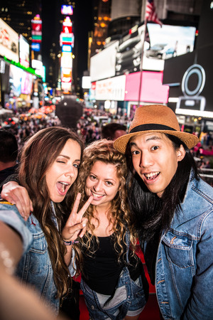 Group of friends taking a selfie in Times Square, Manhattan