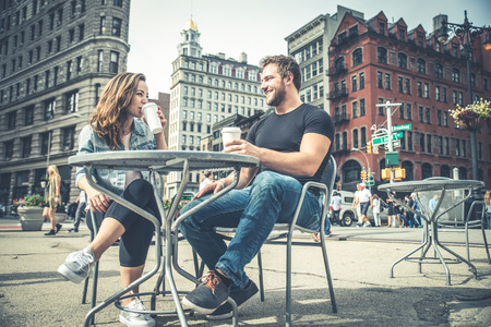 joking: Couple dating in a coffeehouse bar in Manhattan - Tourists talking and having fun while sighseeing New York