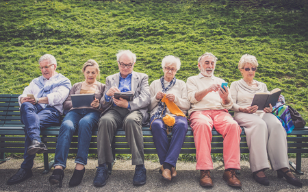 group of friends: Group of senior people resting in a park - Mature friends doing some activities in a retirement home