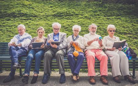Gruppo di gente maggiore che riposa in un parco - amici maturo facendo alcune attività in una casa di riposo