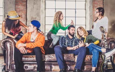 gruppo di razza mista di adolescenti divertirsi sul divano - multi-etnico giovani adulti festa a casa Archivio Fotografico