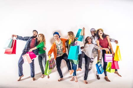 group shot: Multi-ethnic group of people holding colored shopping bags and laughing - Portrait of funny friends posing on white background