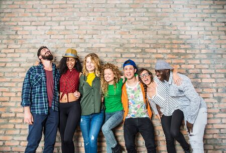 girls youth: Group portrait of multi-ethnic boys and girls with colorful fashionable clothes holding friend in hands and posing on a brick wall - Urban style people having fun, studio shot - Concepts about youth  and togetherness Stock Photo