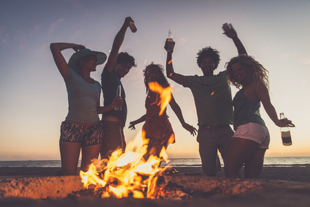 Multicultural group of friends partying on the beach - Young people celebrating during summer vacation, summertime and holidays concepts Banco de Imagens