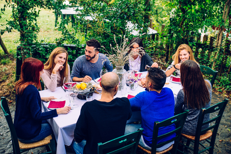 Group of friends at restaurant outdoors - People having dinner in a home garden Stok Fotoğraf - 69031036