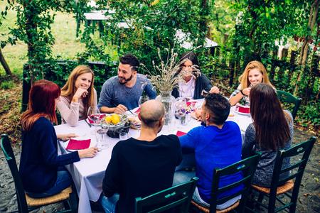 Gruppo di amici al ristorante all'aria aperta - La gente a cena in un giardino di casa Archivio Fotografico