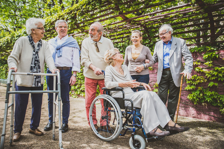 Group of senior people with some diseases walking outdoors - Mature group of friends spending time together Фото со стока