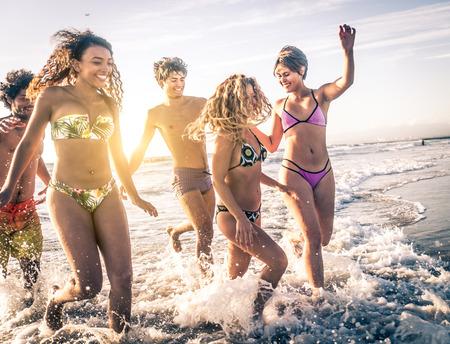 sun beach: Multi-ethnic group of friends running on the beach - Young people having fun in the sea during summer holidays Stock Photo