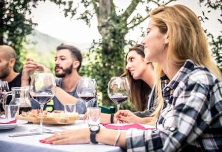 Groep vrienden bij restaurant buitenshuis - Mensen die diner in een huis tuin