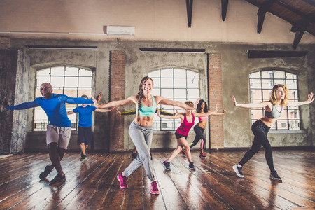 Group of sportive people training in a gym - Multi-ethnic group of athletes doing fitness Stockfoto