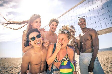 pelota de voley: Grupo de amigos que juegan al voleibol de playa en la playa y divertirse