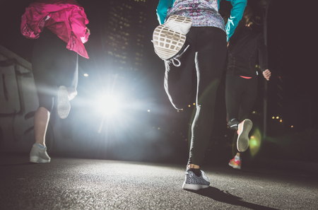 Three women running in the night in the city center Stock Photo