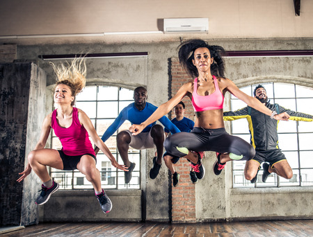 Group of sportive people training in a gym - Multi-ethnic group of athletes doing fitness Stock Photo