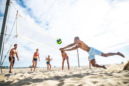 pelota de voley: Grupo de amigos que juegan al voleibol de playa - Grupo Multi-ética de personas que se divierten en la playa