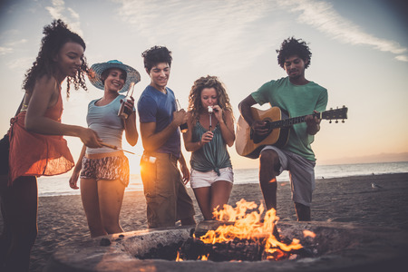 Multicultural group of friends partying on the beach - Young people celebrating during summer vacation, summertime and holidays concepts Stock Photo